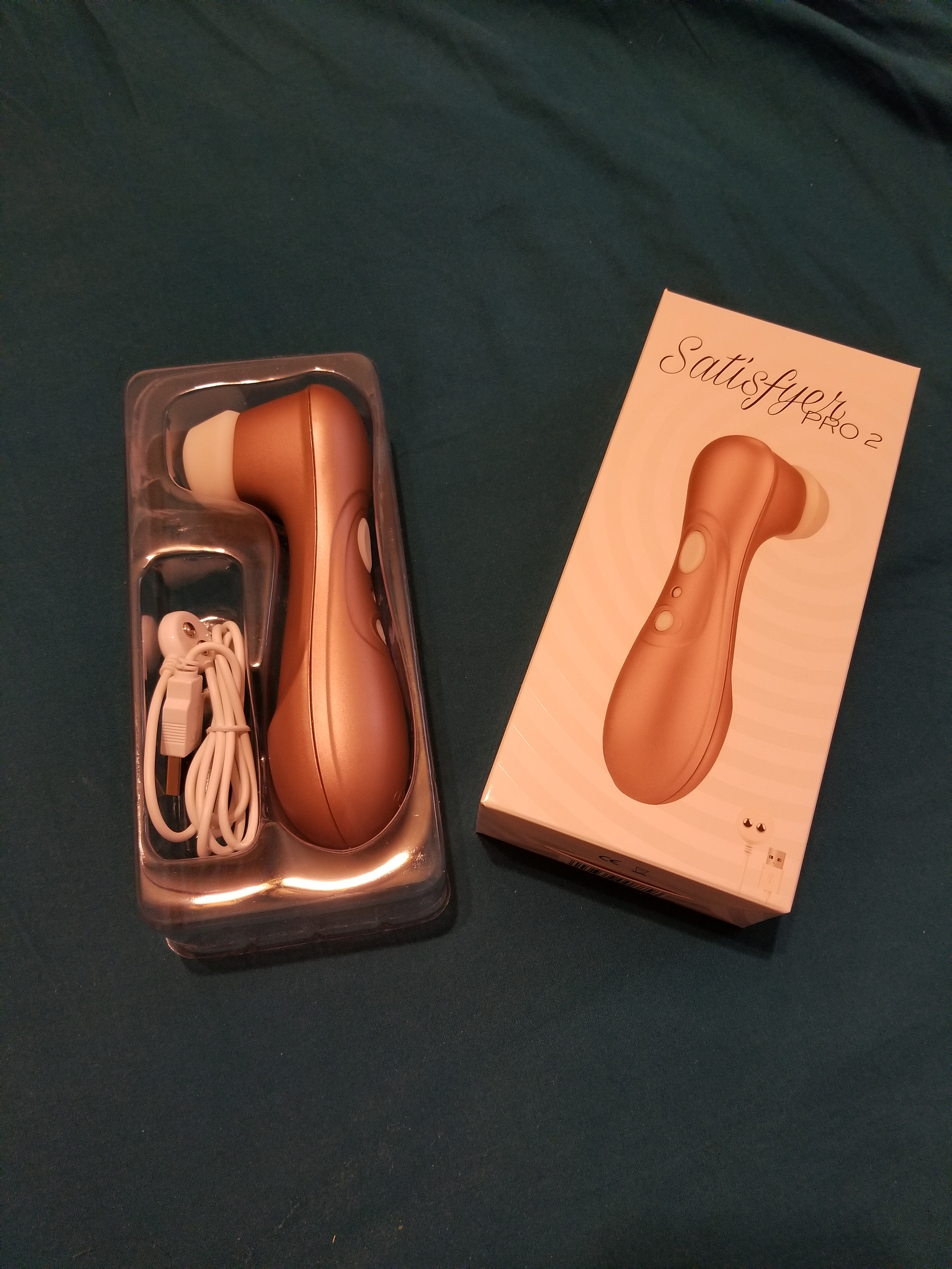 A toy that is copper in color with a white nozzle rests in a plastic cradle. A box sits next to it.