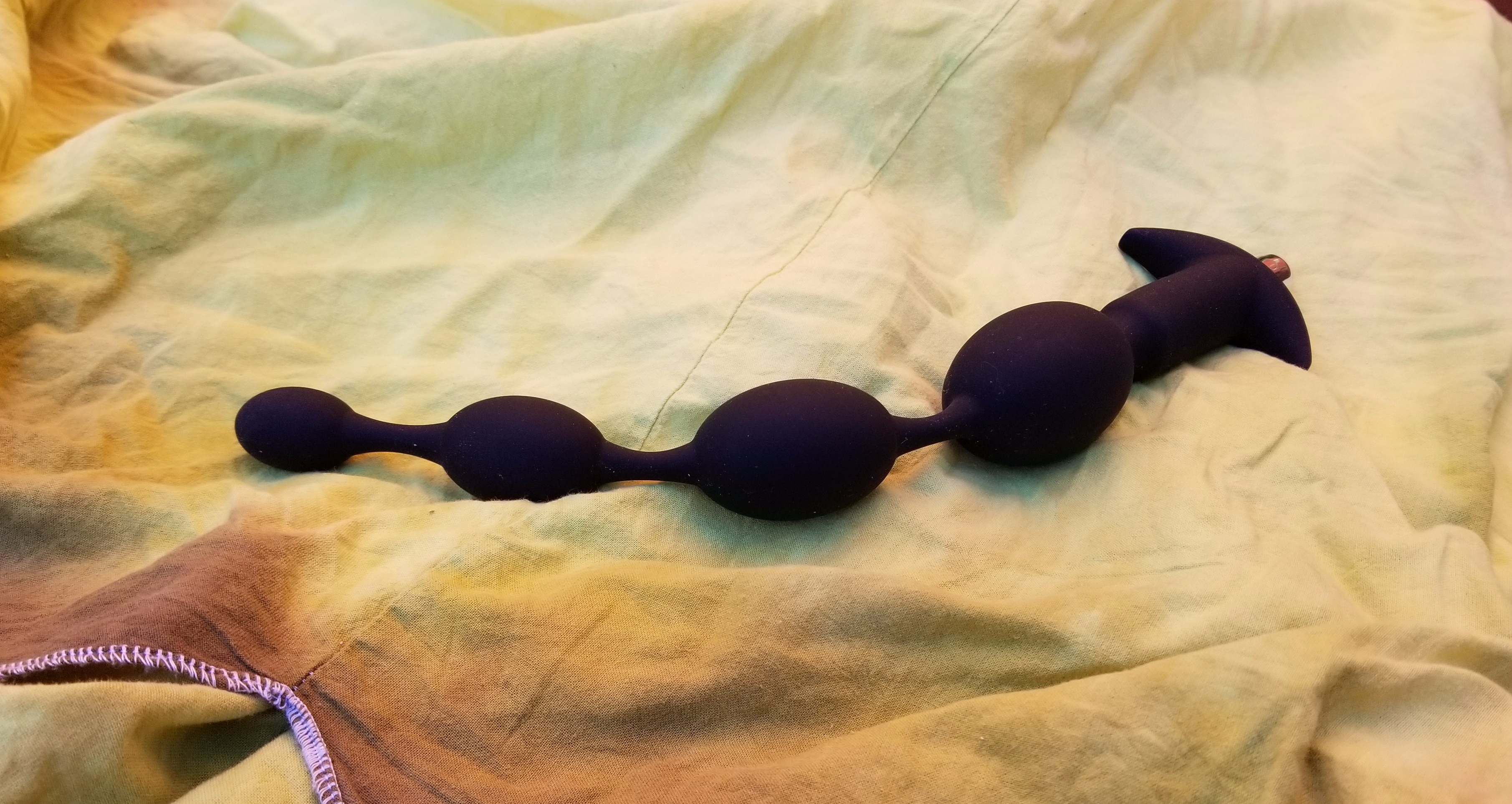 Black silicone anal beads with four beads of progressing size sit on a green fabric. There is a crescent base with a bullet vibe inserted.