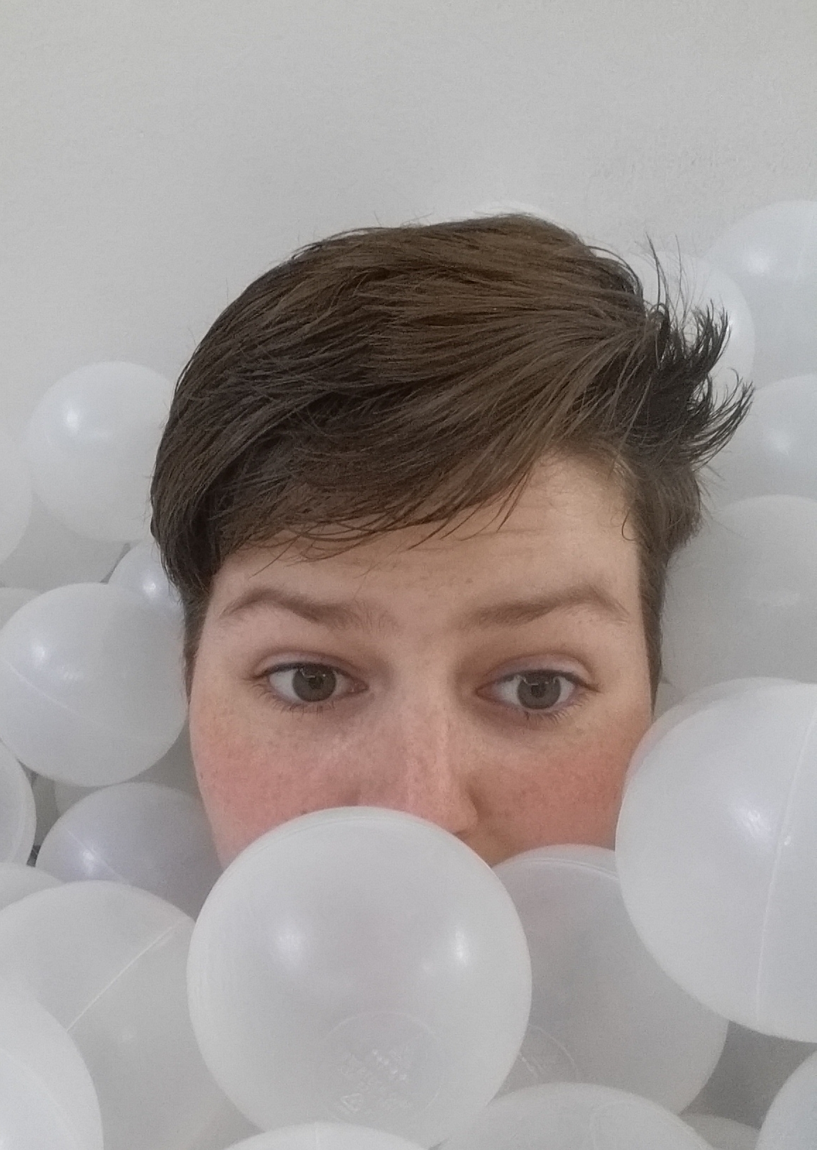 Indigo in a ball pit, covered with white plastic balls. You can see their eyes, perfect freckles and short hair. It is swept to one side and spiked on the other.