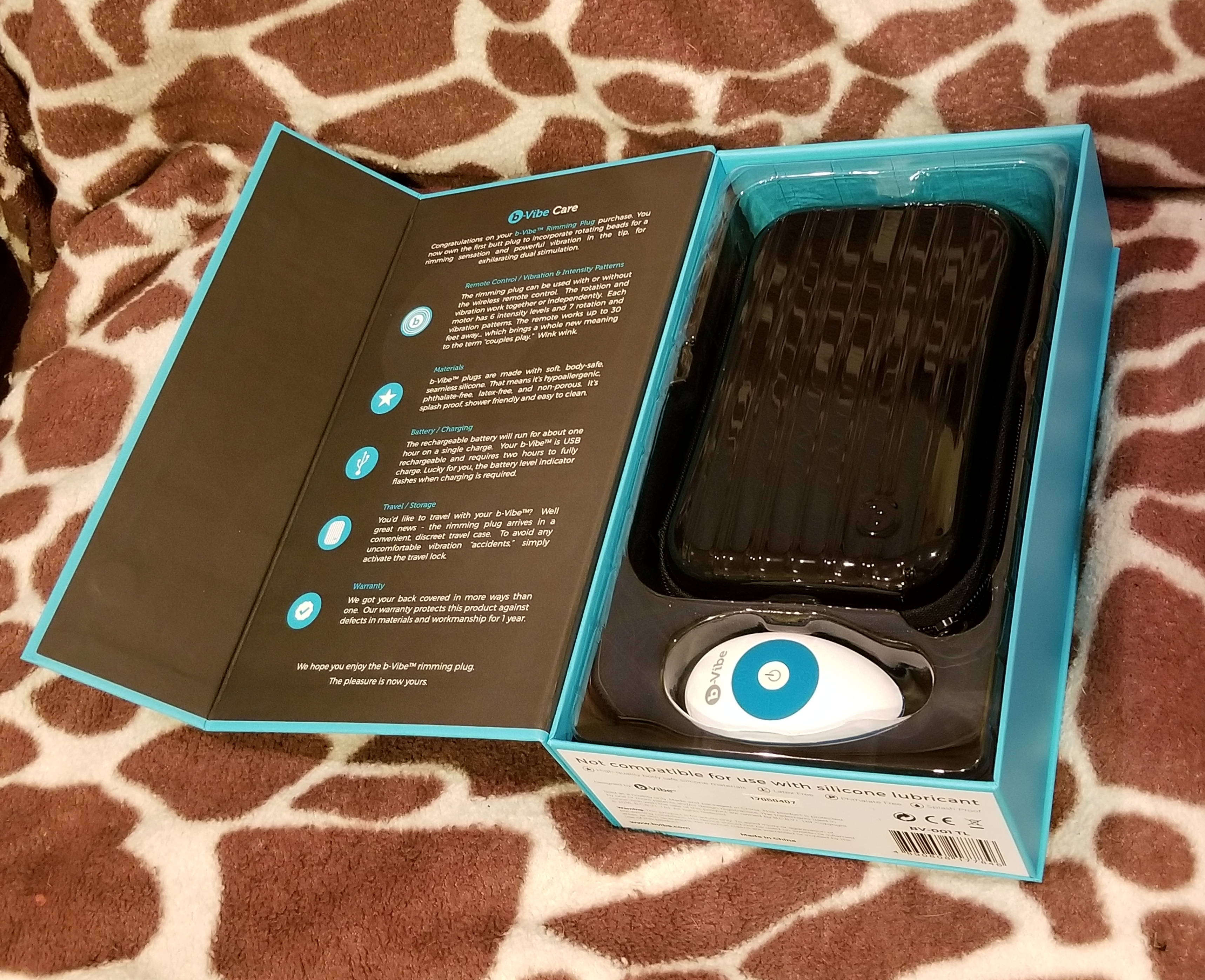 A box with the cover open reveals a black plastic case and a white and teal remote. On the back of the cover is some basic information about the plug.