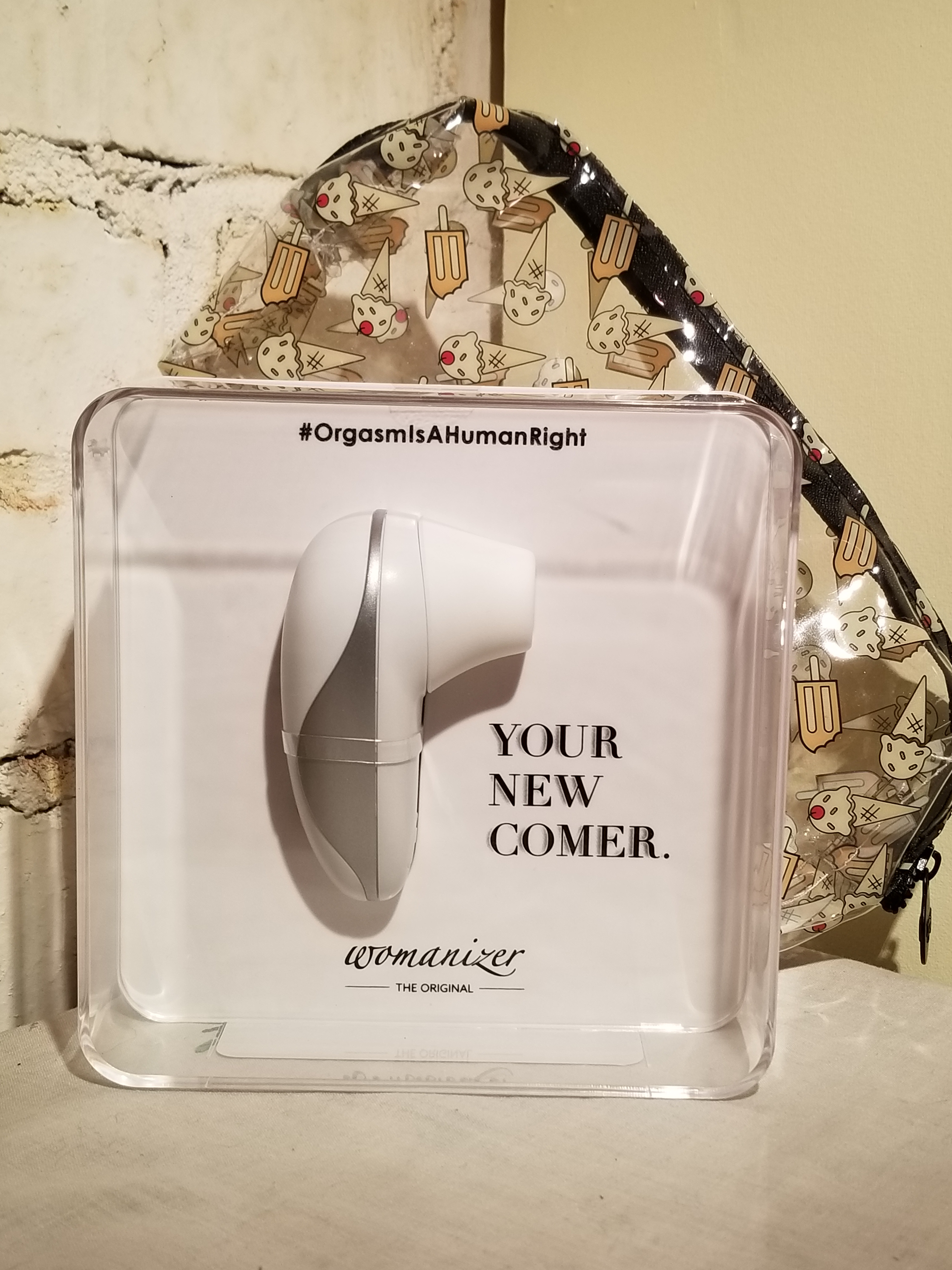 The Womanizer Starlet sits in a clear plastic case. The Starlet is about three and a half inches tall with a nozzle for suction. It is while with silver accents.