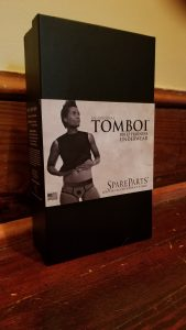 The Spareparts Tomboi box is sitting on a wooden floor with a yellow wall behind it. The box is black and has a picture of a masculine-leaning person on it.