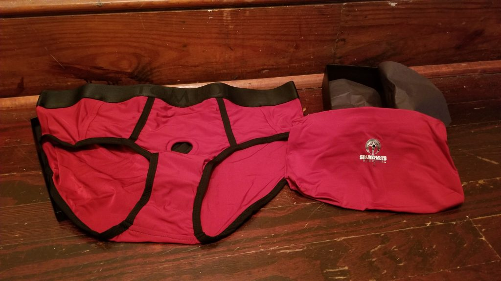 The Spareparts Tomboi is unfolded and laying on a clean wooden floor while the carrying bag lays beside it. The bag is propped up so that you can see the SpareParts logo. The bag is all read nylon. The Tomboi itself is mostly red with a black waistband and black trim. It's shaped roughly like typical men's underwear.