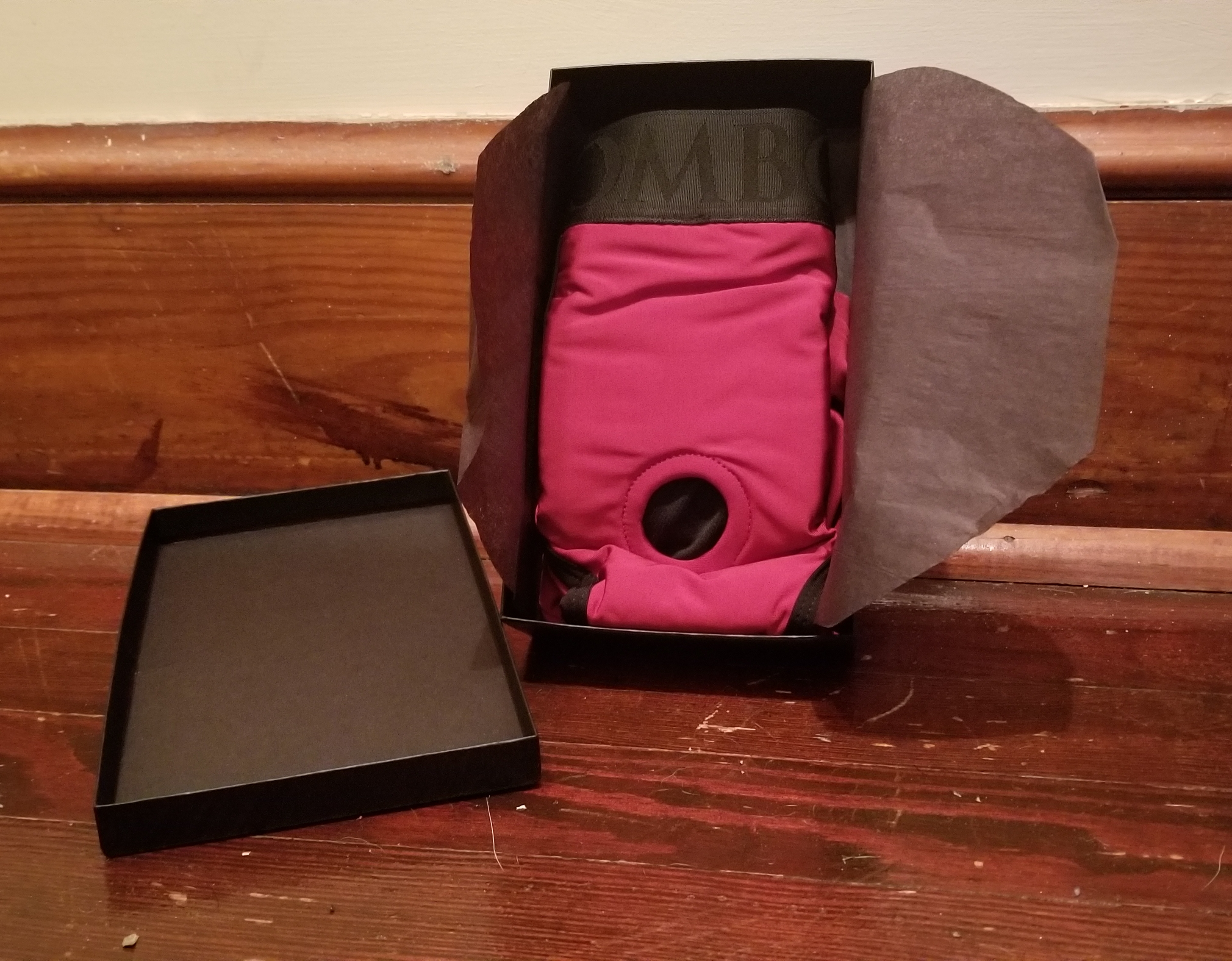 The SpareParts box is open to reveal the front of the Tomboi. It's wrapped with tissue paper. The focus of the photo is the o-ring, which is about an inch in diameter in the center of the Tomboi.