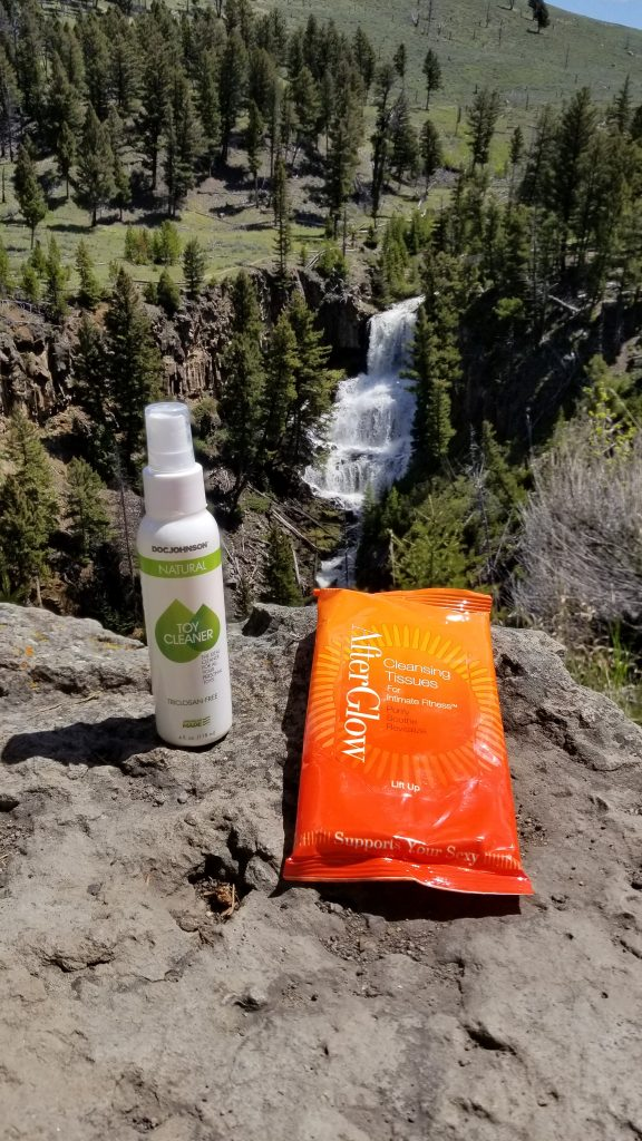 The Doc Johnson Natural Toy Cleaner and the AfterGlow wipes sit on a rock. In the background is a waterfall. It's majestic and invokes thoughts of fresh, clean air.