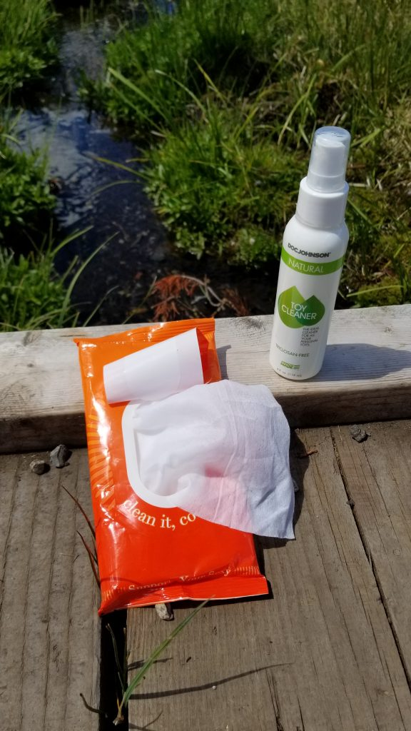 The AfterGlow Wipes sit open to reveal a white wipe sticking out sitting next to the Doc Johnson Toy Cleaner. They are on a wooden boardwalk, and behind is a small stream.