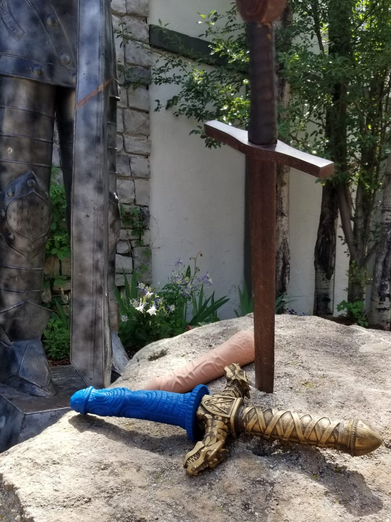 "The Realm handle is attached to the Draken attachment. It looks like a sword with a golden hilt, and the ""blade"" section is a navy blue dildo with a lot of bumps and ridges. They sit on a rock with a realistic attachment next to them. In the rock is a fake sword, which mimics the idea of the Sword in the Stone."